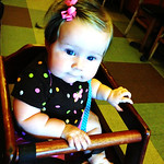 Sitting in a high chair like a big girl.